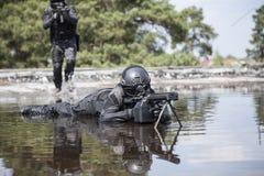 Los oficiales de policía de los ops de espec. GOLPEAN CON FUERZA en el agua Foto de archivo libre de regalías