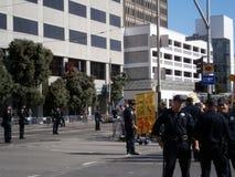 Los oficiales de policía de SFPD se colocan en la calle mientras que la muestra del control de los manifestantes dice Fotos de archivo