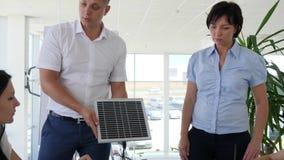 Los oficinistas discuten los paneles solares del desarrollo y de las posibilidades en oficina moderna almacen de metraje de vídeo