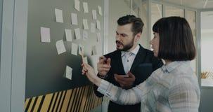 Los oficinistas hacen un plan de trabajo y de pegar todas las ideas en la pared metrajes