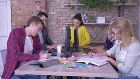 Los oficinistas jovenes activos escriben notas con ideas en los cuadernos y las etiquetas engomadas coloreadas que se sientan en  almacen de metraje de vídeo