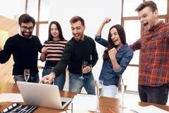 Los oficinistas jovenes que miran el ordenador portátil defienden juntos fotografía de archivo libre de regalías