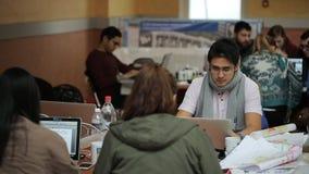 Los oficinistas se sientan en sitio y trabajan en los ordenadores portátiles en tiempo del día almacen de metraje de vídeo