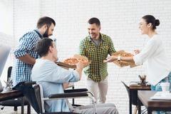 Los oficinistas y el hombre en una silla de ruedas están comiendo la pizza Trabajan en una oficina brillante y moderna imagen de archivo