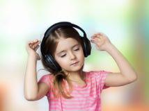 Los ojos cerrados muchacha del niño escuchan los auriculares de la música Imagen de archivo