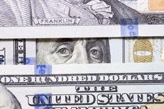 Los ojos de Benjamin Franklin entre cientos primers de los billetes de banco del dólar billete de dólar 100 con solamente los ojo fotografía de archivo libre de regalías