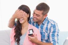 Los ojos de la mujer de la cubierta del hombre mientras que gifting el anillo Imagenes de archivo
