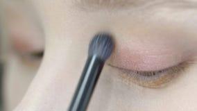 Los ojos de la mujer joven están siendo coloreados por el visagist, cierre para arriba almacen de video