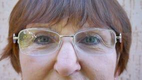 Los ojos de la mujer mayor con los vidrios están mirando metrajes