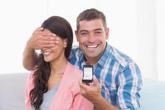Los ojos del hombre de la mujer feliz de la cubierta mientras que gifting el anillo Imagenes de archivo