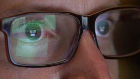 Los ojos del hombre del primer en vidrios trabajan en el ordenador portátil en la noche almacen de video