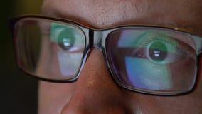 Los ojos del hombre del primer en vidrios trabajan en el ordenador portátil en la noche almacen de metraje de vídeo