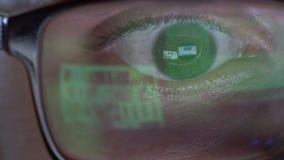 Los ojos del hombre del primer en vidrios trabajan en el ordenador portátil en la noche metrajes