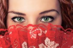 Los ojos y la cara de la mujer ocultan con la fan roja Foto de archivo libre de regalías
