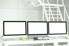 Los ordenadores modernos tienen pantallas y documentos de negocio blancos en blanco imagenes de archivo
