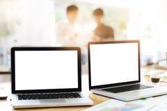 Los ordenadores portátiles en oficina con trabajo en equipo del negocio discuten fotos de archivo libres de regalías