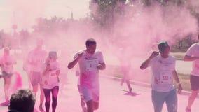 Los organizadores lanzan, lanzan el holi de la pintura, rosa, color, frente a los corredores de maratón que corren a lo largo de  almacen de metraje de vídeo