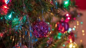 Los ornamentos brillantemente coloreados, alegres del árbol de navidad colgaron para arriba con las luces y la malla imagen de archivo
