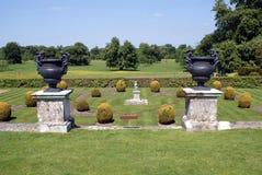 Los ornamentos del vintage en pedestales en un topiary cultivan un huerto Imágenes de archivo libres de regalías