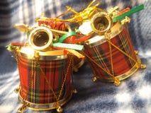 Los ornamentos lindos del tambor de la Navidad se cierran para arriba contra fondo de la tela escocesa fotografía de archivo libre de regalías