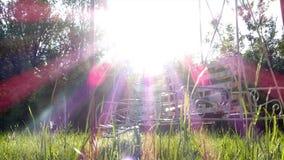 Los oscilaciones vacíos de balanceo contra el sol se encienden con efecto luminoso soñador almacen de metraje de vídeo