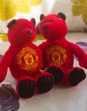 Los osos de peluche del Manchester United se abrazan mientras que establecen abajo para mirar un partido de fútbol en la TV Fotos de archivo