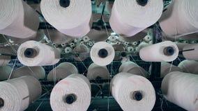 Los ovillos que arrollan funcionan con los hilos blancos en un estante de la fábrica metrajes