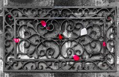 Los pétalos de rosas se dispersan en un enrejado forjado fotografía de archivo libre de regalías