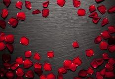 Los pétalos de Rose confinan el fondo en una placa negra de la piedra de la pizarra Fotos de archivo