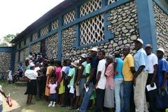 Los pacientes de la clínica hacen cola para arriba en pueblo haitiano Imágenes de archivo libres de regalías
