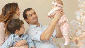 Los padres adultos jovenes con sus pequeños niños en la Navidad miden el tiempo en casa almacen de video