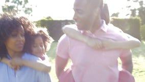 Los padres afroamericanos que dan a niños llevan a cuestas paseos almacen de video