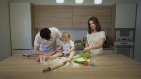 Los padres as? como una peque?a hija est?n cocinando en la cocina en casa El concepto de felicidad de la familia almacen de metraje de vídeo
