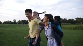 Los padres asiáticos que dan a niños llevan a cuestas paseo en parque almacen de video