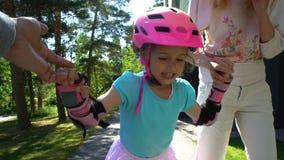 Los padres ayudan a su pequeña hija a patinar en pcteres de ruedas metrajes