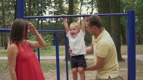 Los padres balancean a un niño en la barra en el parque metrajes