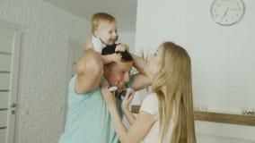 Los padres caucásicos jovenes juegan con su bebé en casa La diversión, risa, padre guarda al niño en sus hombros Un lindo almacen de metraje de vídeo
