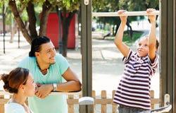 Los padres con el entrenamiento del adolescente encendido levantan la barra Fotos de archivo
