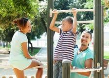 Los padres con el entrenamiento del muchacho encendido levantan la barra Imagen de archivo