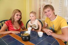 Los padres con el niño beben té en el sitio 2 fotos de archivo