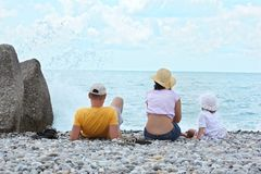 Los padres con el niño se sientan en la costa, visión trasera Fotos de archivo
