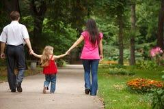 Los padres con la hija recorren en jardín del verano Fotos de archivo libres de regalías