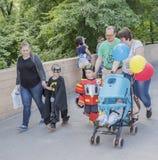 Los padres con los niños en trajes del carnaval están caminando en el st Imagen de archivo libre de regalías