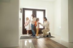 Los padres consiguen niños listos para el paseo de la escuela que se coloca en el vestíbulo Imagenes de archivo