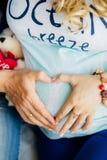 Los padres dan la fabricación del corazón en el vientre de la madre embarazada Fotografía de archivo libre de regalías
