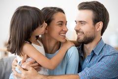 Los padres de amor relajan el abrazo con poca hija en casa imágenes de archivo libres de regalías