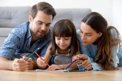Los padres de amor relajan el dibujo as? como peque?a hija foto de archivo