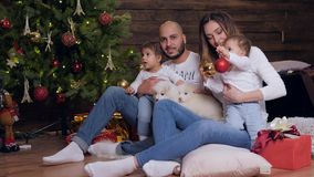Los padres de la Navidad detienen a niños y los perritos, la mamá joven y el papá mira la cámara en árbol iluminado fondo de Navi almacen de metraje de vídeo