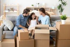 Los padres emocionados se relajan en el sofá con la hija en día móvil foto de archivo