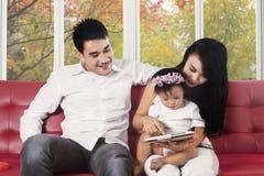 Los padres enseñan a su niño con la tableta digital Fotos de archivo libres de regalías
